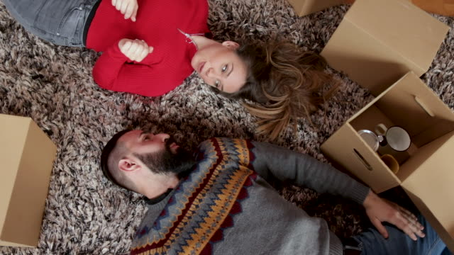 beautiful couple lying down on carpet in living room and having fun - lying on back stock videos & royalty-free footage