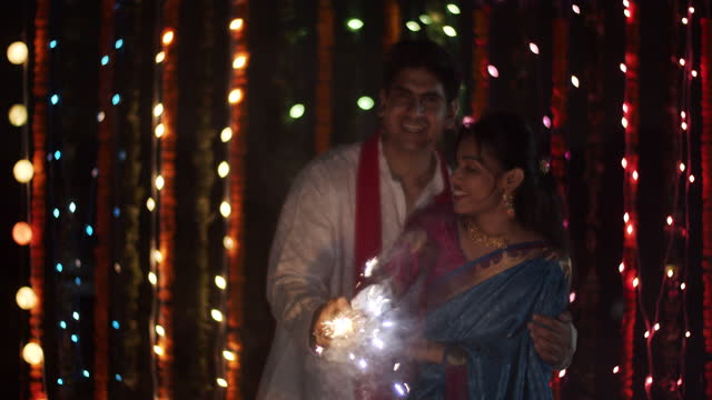 beautiful couple namaste greet looking at camera pov and then light a firework cracker to illumiate the night on a terrace in a romantic setting with a decorated backdrop with lights xmas and flowers - short phrase stock videos & royalty-free footage