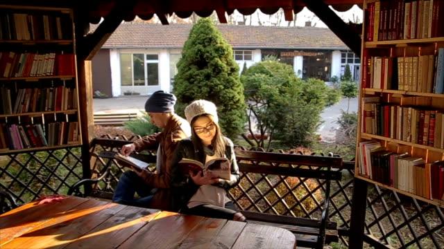 vidéos et rushes de beau couple sur un rendez-vous romantique bouquiner en plein air - littérature