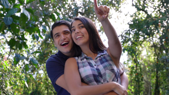 vídeos de stock e filmes b-roll de beautiful couple outdoors hugging and looking at the view - mostrar