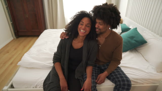 stockvideo's en b-roll-footage met beautiful couple relaxing while sat on a bed - dubbel bed