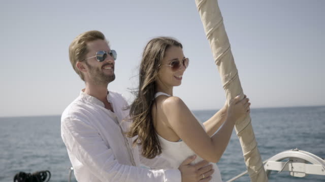 vídeos de stock e filmes b-roll de beautiful couple sailing on catamaran - greece