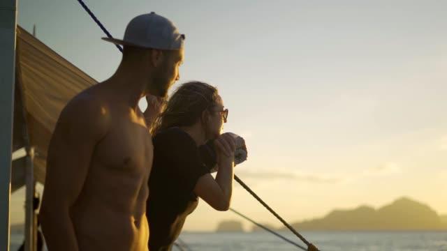 bella coppia che naviga sul mare al tramonto - barca da diporto video stock e b–roll