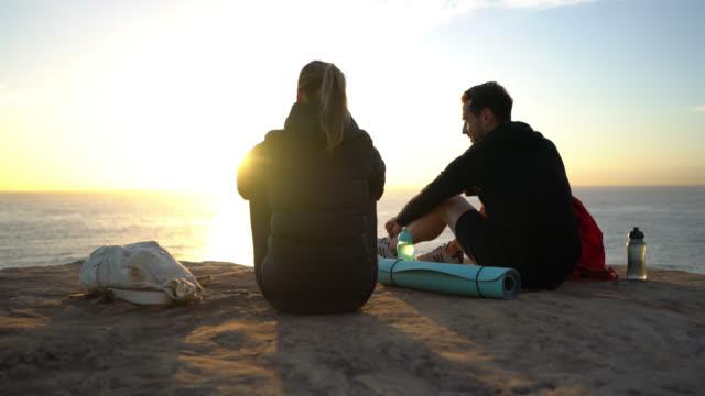 schönes paar eine pause sitzen auf klippe sprechen und das betrachten - ökotourismus stock-videos und b-roll-filmmaterial