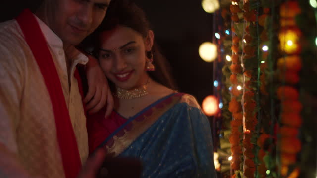 beautiful couple taking romantic photos videos alone on the terrace at night in traditional clothes as they look at each other and smile and look like they are made for each other on a special night - short phrase stock videos & royalty-free footage