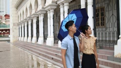 vídeos de stock, filmes e b-roll de lindo casal passando o sultão abdul samad building, em um dia chuvoso - edifício do sultão abdul samad