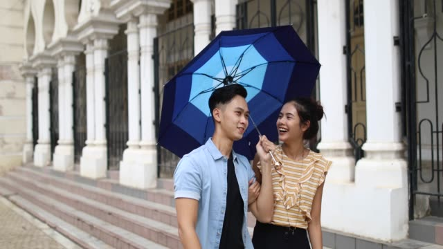 beautiful couple walking by the sultan abdul samad building, on a rainy day - cultura malesiana video stock e b–roll