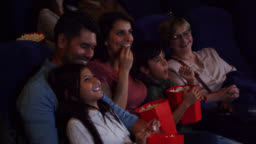 Beautiful couple with their two kids and grandmother enjoying a movie at the cinema while eating snacks