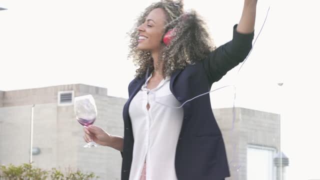 vídeos y material grabado en eventos de stock de hermosa mujer morena rizada bailando en una hermosa tarde desde sus auriculares en la terraza de su casa - 30 39 years
