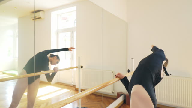 Beautiful dancer stretching and exercising at the barre.
