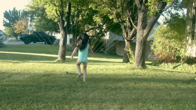beautiful dark haired school aged girl running through a sprinkler having a great time being refreshed and cooled off during a hot summer day - sprinkler stock videos & royalty-free footage