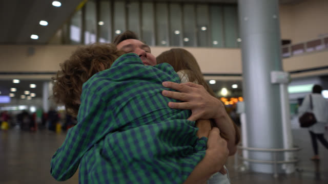 beautiful daughter and son greeting their dad with excitement at the airport hugging him - embracing stock videos & royalty-free footage