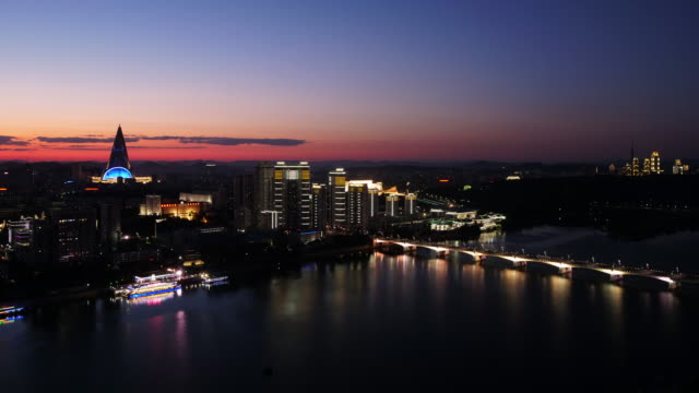 beautiful day to night time lapse pyongyang skyline with pyramid (ryugyong hotel) and modern buidlings at taedong river,  in north korea, dprk. sunset seen from juche tower. - spoonfilm stock-videos und b-roll-filmmaterial