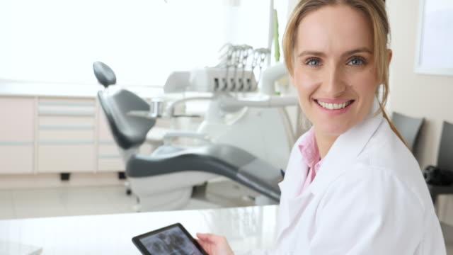 vídeos de stock, filmes e b-roll de bela dentista com tablet - saúde dental