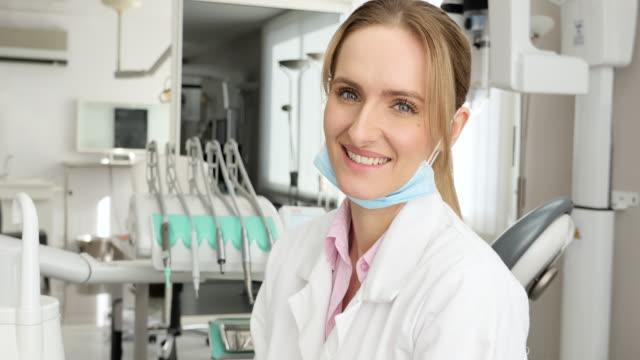vidéos et rushes de belle dentiste avec le pouce vers le haut - gant de chirurgie