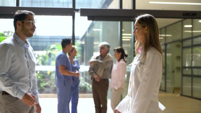schöner arzt begrüßt männlichen patienten mit einem handschlag im krankenhaus - grüßen stock-videos und b-roll-filmmaterial