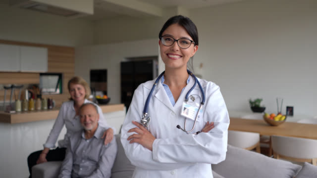beautiful doctor on a house call of a senior couple facing camera smiling with arms crossed - house call stock videos & royalty-free footage