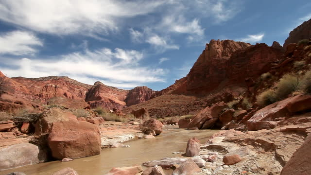 beautiful dramatic cirrus clouds against deep blue sky overlooking river and red rock desert landscape. - red rocks stock videos & royalty-free footage