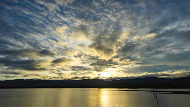 beautiful dramatic sky over mountains and lake at sunrise, time lapse video - tree trunk stock videos & royalty-free footage