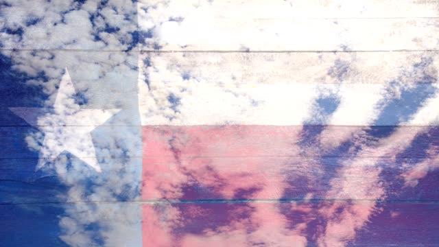 schöne treibende wolken ausgeblendet, wie texas state flag in den fokus kommt. - fade in video transition stock-videos und b-roll-filmmaterial
