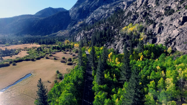 beautiful drone shot on a lonesome road in the california mountains as the trees are changing colors. - yosemite national park stock videos and b-roll footage