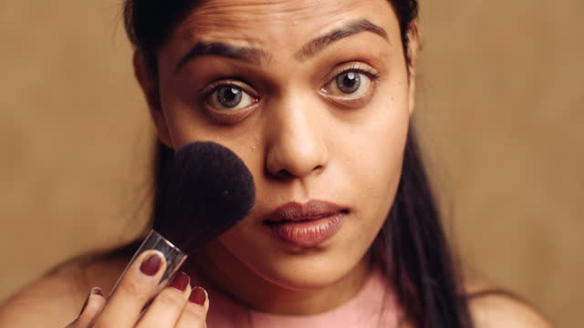 beautiful dusky woman looking at mirror pov as she uses a makeup brush to highlight her beautiful face and clear it off blemishes. she is a perfectionist and thorough - menschlicher finger stock-videos und b-roll-filmmaterial