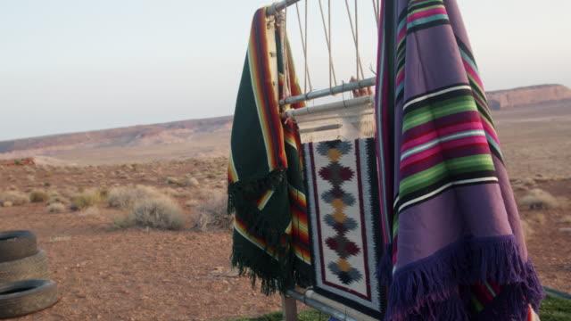 アリゾナ砂漠の広大なモニュメントバレー部族公園の美しい高齢者ネイティブアメリカンナバホ女性は、昔ながらの織機を使用して伝統的なインドの毛布を作ります - インディアン居留地点の映像素材/bロール