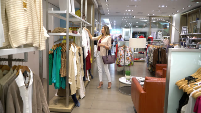 beautiful elegant women looking at clothes from different racks at a women's store - rack stock videos & royalty-free footage