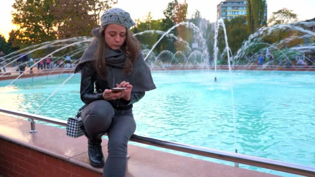 Beautiful elegantly dressed girl sitting near fountain using her smart phone