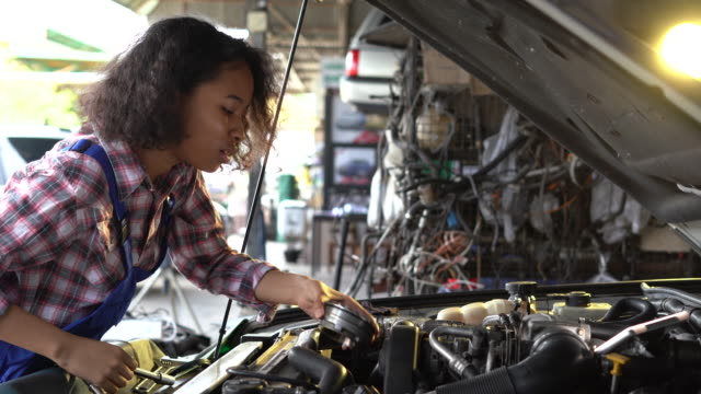 beautiful empowering female mechanic is working on a car in a car service. woman in safety glasses is fixing the engine. she's using a ratchet. modern clean workshop with vehicles. - wrench stock videos & royalty-free footage