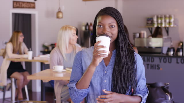 beautiful ethnic female holding hot drink smiling - fatcamera stock videos & royalty-free footage