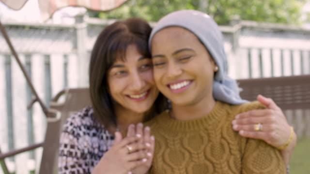 vídeos de stock, filmes e b-roll de fêmea étnica bonita com cancro que abraça sua mamã - radioterapia