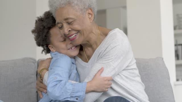 vídeos de stock, filmes e b-roll de a avó étnica bonita está rindo com sua neta nova. - avó