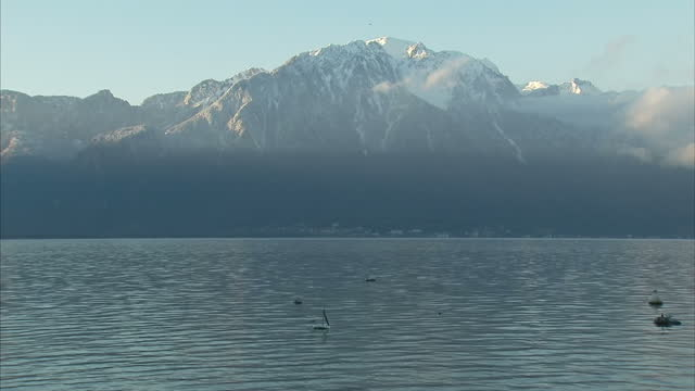 beautiful exterior shots of lake geneva with the alps in the background; river police boat gendarmerie at beginning on in montreux, switzerland. - montreux stock videos & royalty-free footage
