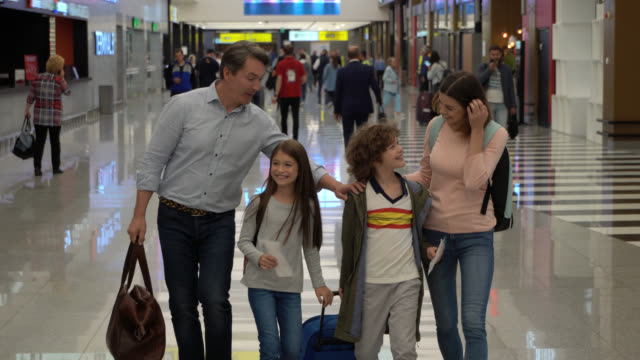 beautiful family walking through airport with their luggage holding passports and boarding passes talking - aeroplane ticket stock videos & royalty-free footage