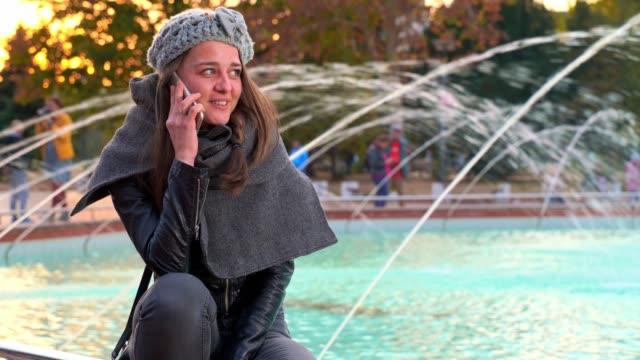 beautiful fashionable girl sitting near fountain talking on phone - bulgaria stock videos & royalty-free footage