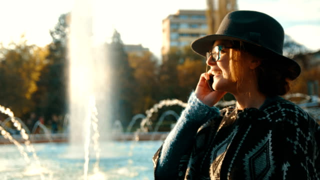 Beautiful fashionable girl standing in front of a running fountain and talking on the phone