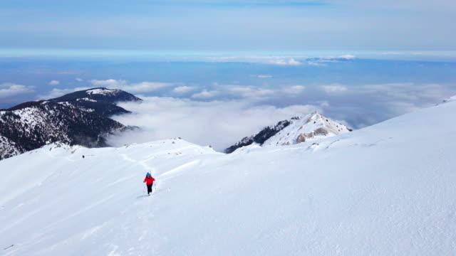 美しい女性の高山登山家は、冬に高地の山の頂上に登っています - winter点の映像素材/bロール