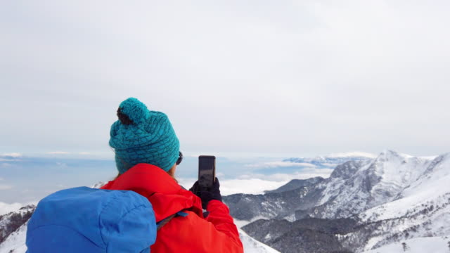 beautiful female alpine mountain climber taking photos with mobile phone in the summit of a high altitude mountain in winter - extreme terrain stock videos & royalty-free footage