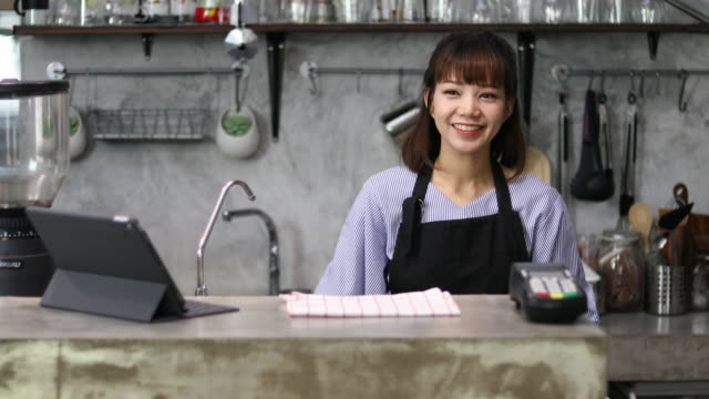 beautiful female barista takes a female customer's order in a local coffee shop - shop assistant stock videos & royalty-free footage
