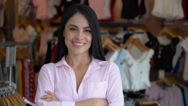 vídeos de stock e filmes b-roll de beautiful female business owner of a clothing store facing camera with arms crossed smiling - boutique