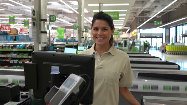 beautiful female cashier working at a supermarket smiling at camera very cheerfully - cashier stock videos & royalty-free footage