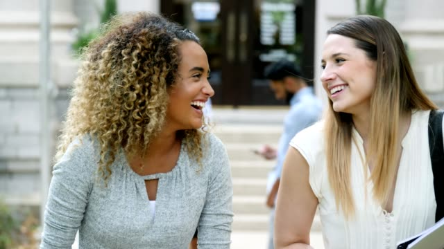 Beautiful female college students laugh while walking on campus