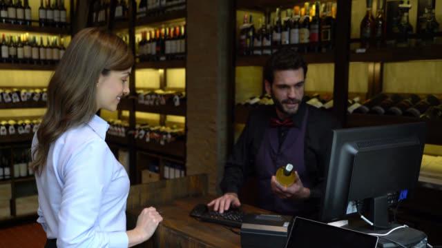 地下室でワインボトルを支払う美しい女性の顧客と彼女のクレジットカードを返すフレンドリーな男性のレジ - ワインバー点の映像素材/bロール