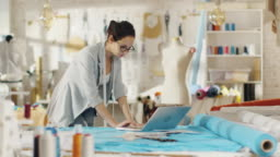 Beautiful Female Designer Uses Laptop on Her Desk that is Covered with Various Fabrics and Sewing Items. Her Studio is Sunny, There is Mannequin, Clothes Hanging and Sketches Pinned to the Wall.