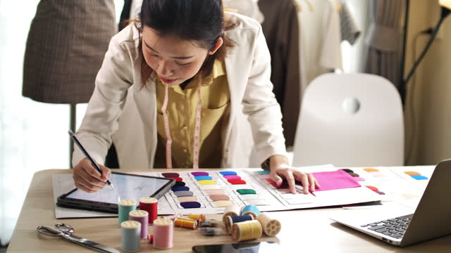 beautiful female designer uses laptop on her desk - textile stock videos & royalty-free footage