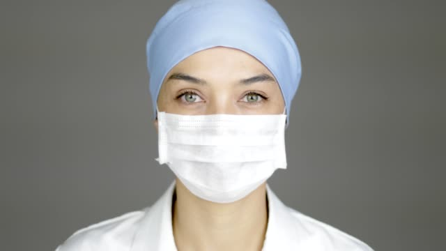 beautiful female doctor or nurse looking to the camera. she is ready for surgery. - surgical mask stock videos & royalty-free footage
