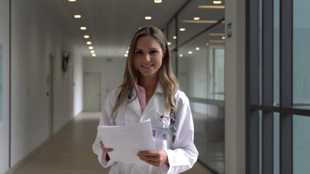 beautiful female doctor reading paperwork and then facing camera smiling - clinic stock videos & royalty-free footage