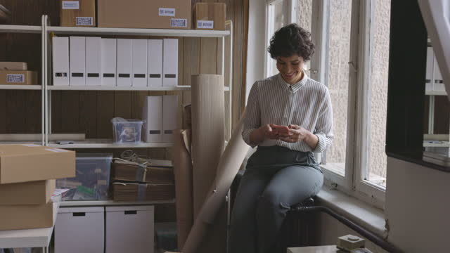 beautiful female entrepreneur sitting by the window and using her smart phone - sitting stock videos & royalty-free footage