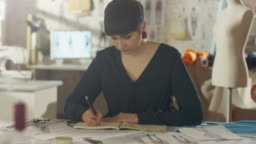 Beautiful Female Fashion Designer Artist Sitting at Her Desk Drawing Sketches for the New Clothing Collection. Her Studio is Bright and Sunny. We See Various Sewing Items, Machines, Sketches, Rolls of Colourful Fabrics.